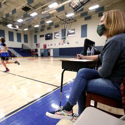 Whitney Childers keeps the game sheets while watching her son Kai Flickinger play in a youth basketball game at Providence Hall Junior High in Herriman on Saturday, Dec. 19, 2020.