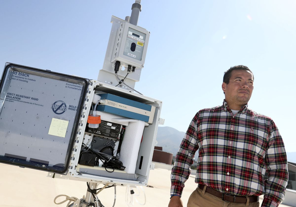 Daniel Mendoza, a professor in atmospheric science, pulmonary medicine and metropolitan planning, is photographed with an air quality monitoring station on the roof of the Spence and Cleone Eccles Football Center at the University of Utah in Salt Lake City on Friday, Sept. 23, 2021.